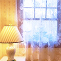 table top lamp by window with lace curtain